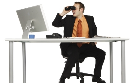 A man sitting at a desk with a computer, a phone and some paperwork looking through a pair of binoculars.