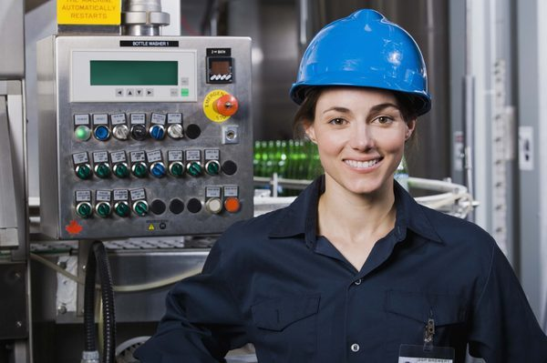Woman wearing a hard hat standing in front of a control panel in an industrial setting