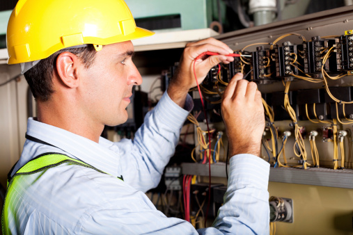 Man wearing a hard hat working on an electrical circuit