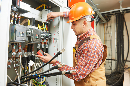 Man wearing a hard hat at an electrical control panel taking readings