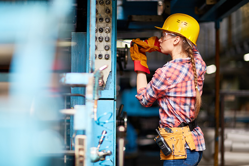 Woman wearing a hard hat and work gloves using a screw driver to make adjustments to an industrial machine