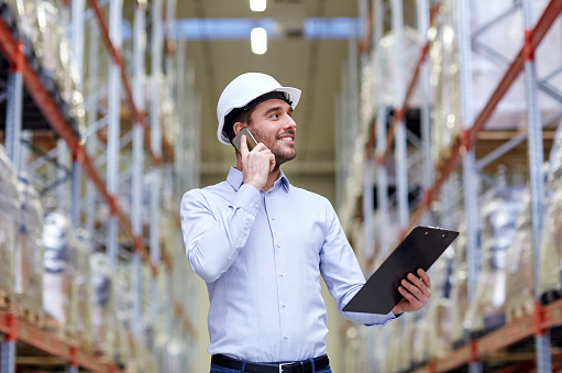 Photograph of a man wearing a hardhat looking at a clipboard and talking on the phone