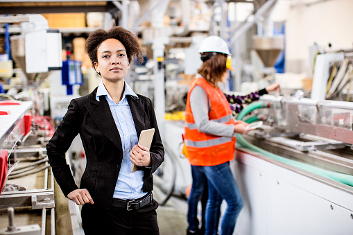 Professional woman holding a tablet standing in a technical or industrial setting with technicians in the background