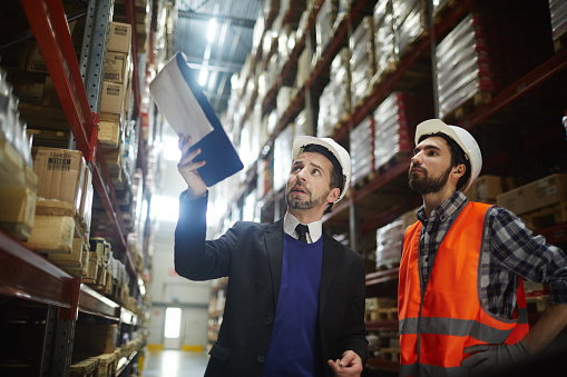 Photograph of two men wearing hardhats inside a warehouse