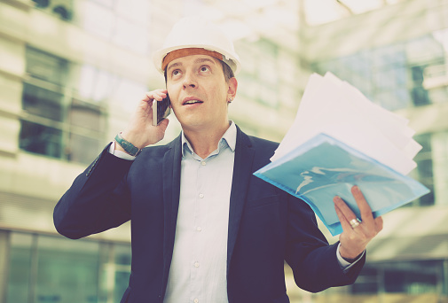 Photograph of a man wearing a hardhat talking on the phone and holding a stack of papers