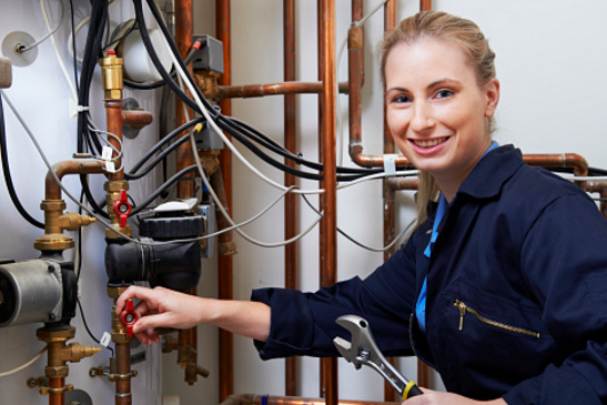 Female plumber holding a wrench fixing pipes