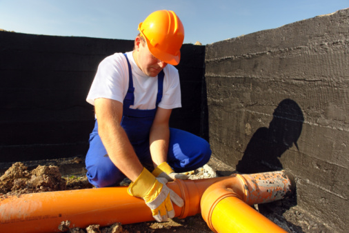 Worker wearing a hard hat laying a large pipe on a construction site