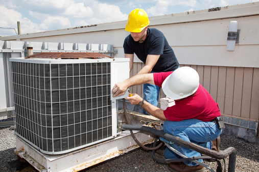 Two workers in hard hats working on an air conditioning unit on the roof of a commercial building