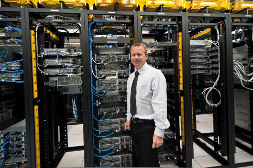 Man posing in front of several racks of servers
