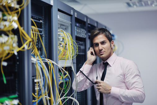 Man testing connections on servers with lots of wires