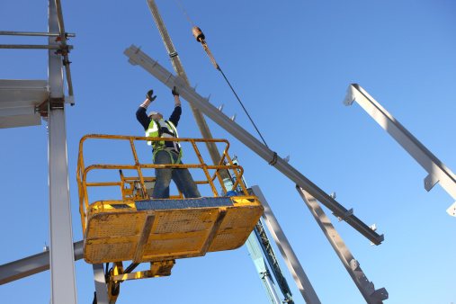 Construction worker on a lift guiding a beam into place that is held in mid-air by a crane