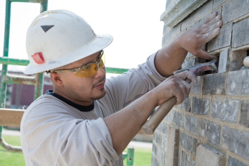 Man wearing a hard hat fixing a brick wall
