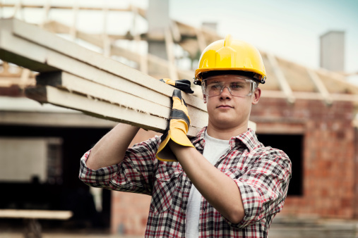 Male construction worker wearing a yellow hard hat carrying boards on his shoulder at a house construction site