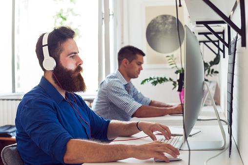Two men sitting at computer stations