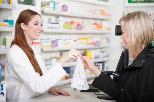 Pharmacist handing a customer a bag with a prescription and smiling