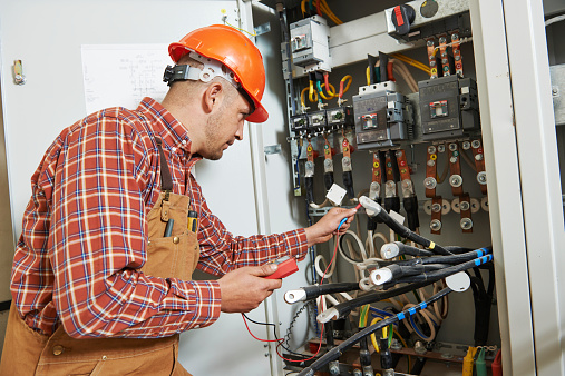 Electrician wearing a hard hat testing electrical panel
