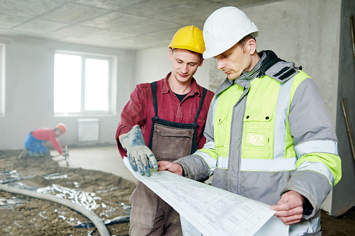 Two construction workers wearing hard hats consulting plans in the interior of a building under construction