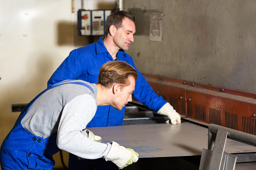 Two men wearing coveralls and work gloves manipulating some sheet metal