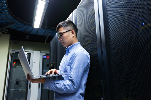 Man holding a laptop in front of a rack of servers