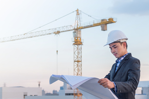 Man wearing a hard hat holding architectural plans with crane in the background