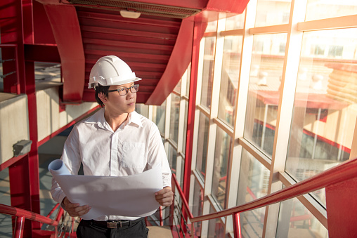 Man wearing a hard hat holding plans looking out the window of an office building