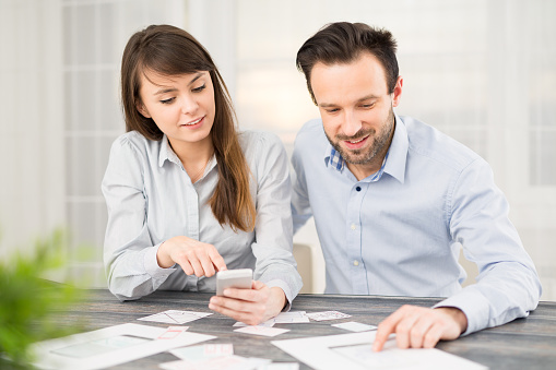 A man and a woman sitting at a desk with bits of paper arranging them in order