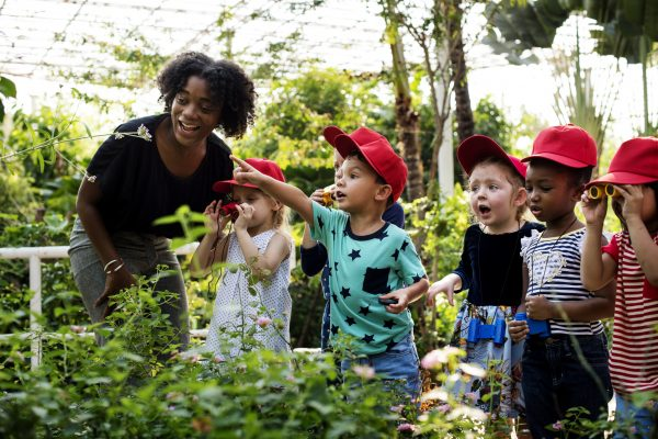 Female teacher leading five young children on a tour of a botanical garden