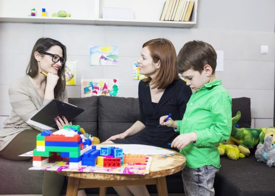 School administrator smiling at a mother and young son in an educational office meeting setting